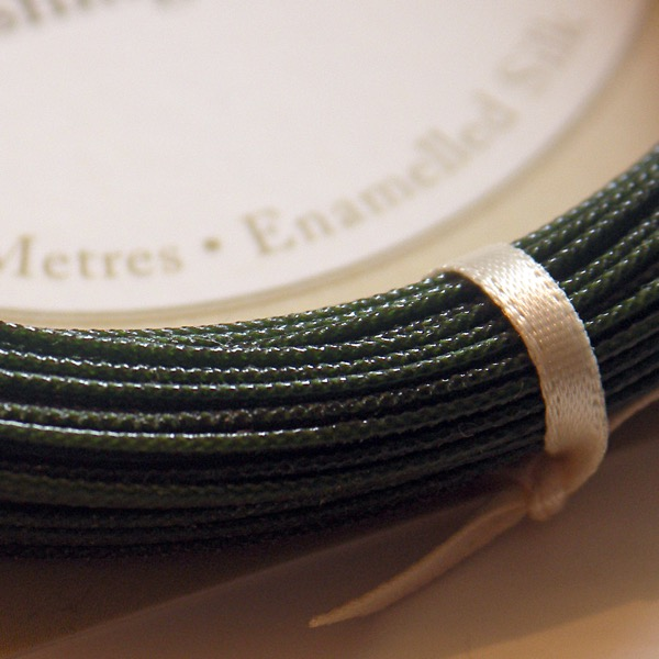 Close up detail of a braided silk fishing line in a mere green colour.