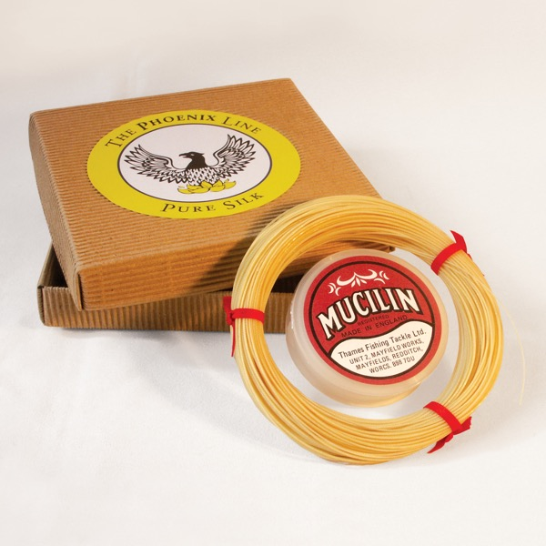 Product photograph of fishing line in straw colour with packaging and a tin of Red Mucilin.